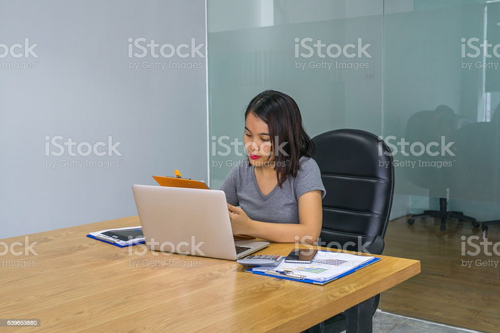 Woman reading report while working overtime alone at office stock photo
