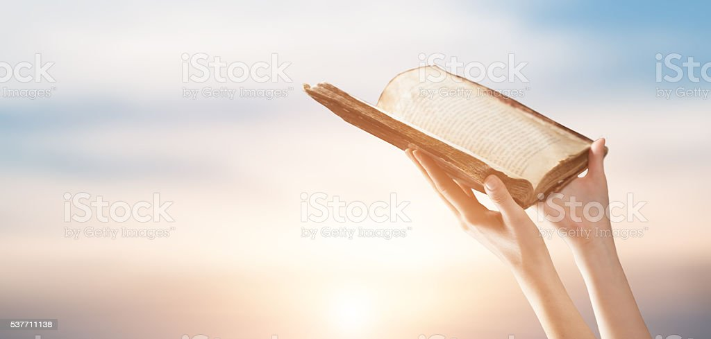 woman reading the bible in the darkness stock photo