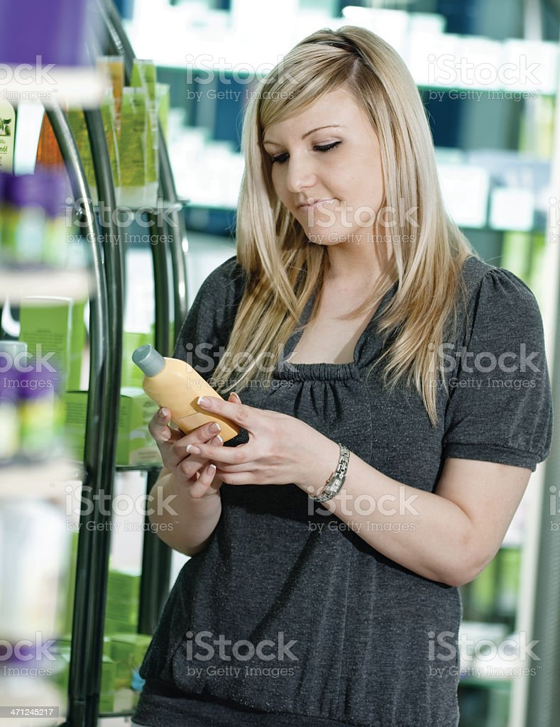 Woman Reading the Lable On Cosmetic Bottle royalty-free stock photo