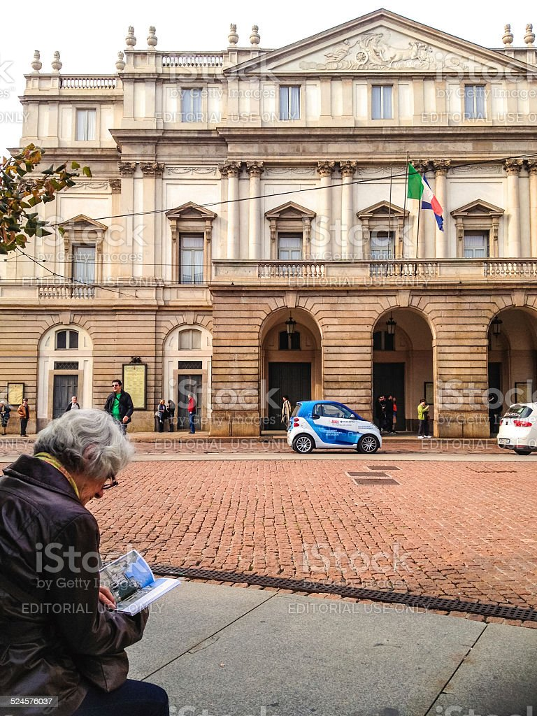 Senior Woman reading travel guide in front of La Scala, Milan