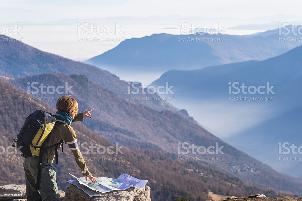 Woman reading trekking map and poiting finger to the Alps stock photo