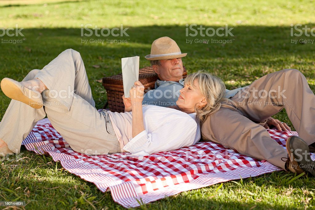 Woman reading while her husband is sleeping in the park royalty-free stock photo