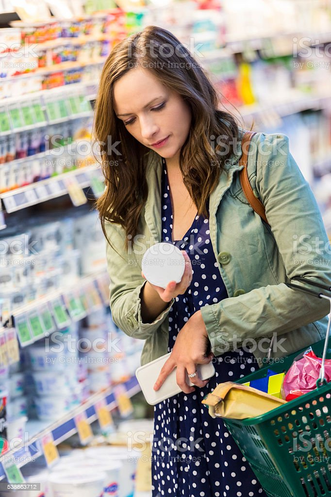 Woman reading yogurt label stock photo