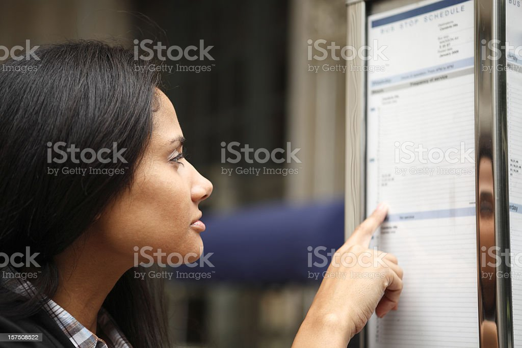Woman Reads Bus Schedule royalty-free stock photo