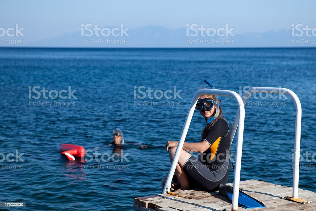Woman ready to dive, man is waiting her royalty-free stock photo