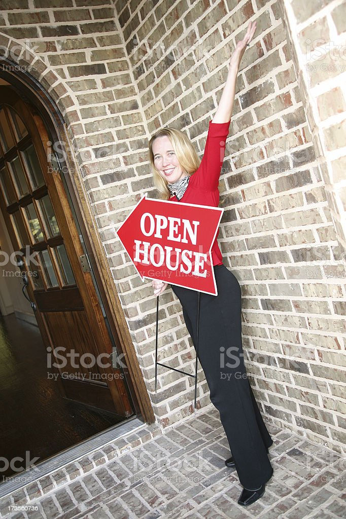 Woman Realtor Welcoming Buyers To Open House stock photo