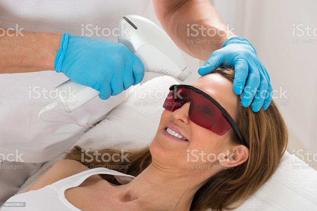Woman Receive Laser Epilation In Beauty Clinic stock photo