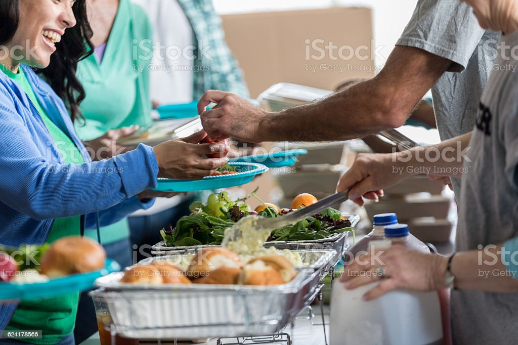 Woman receives a healthy meal at soup kitchen stock photo
