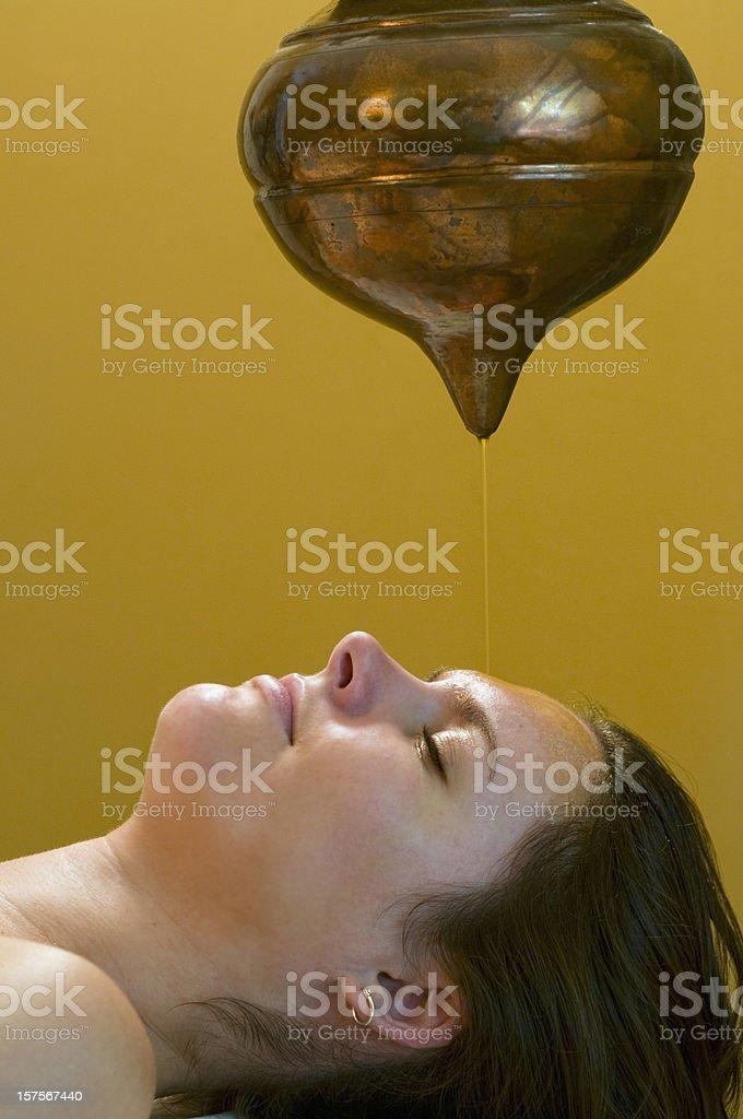 Woman receives holistic Shirodhara Third-Eye Oil Drip Treatment royalty-free stock photo
