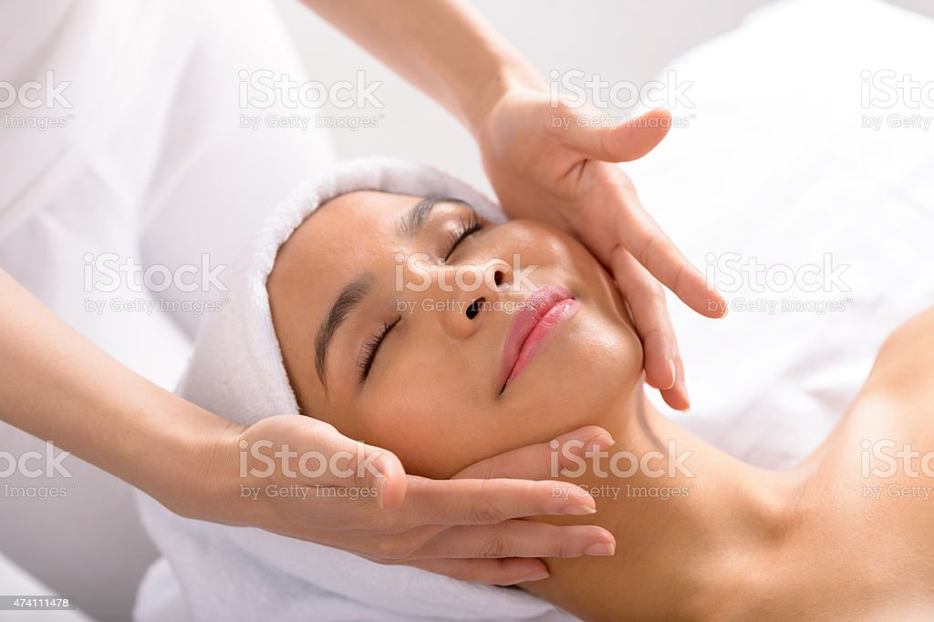 A woman receiving a face massage in a spa stock photo