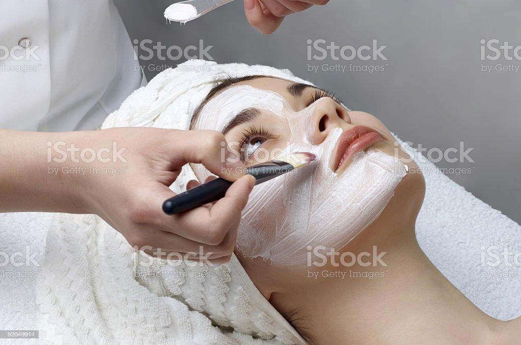 Woman receiving a facial mask at a spa royalty-free stock photo