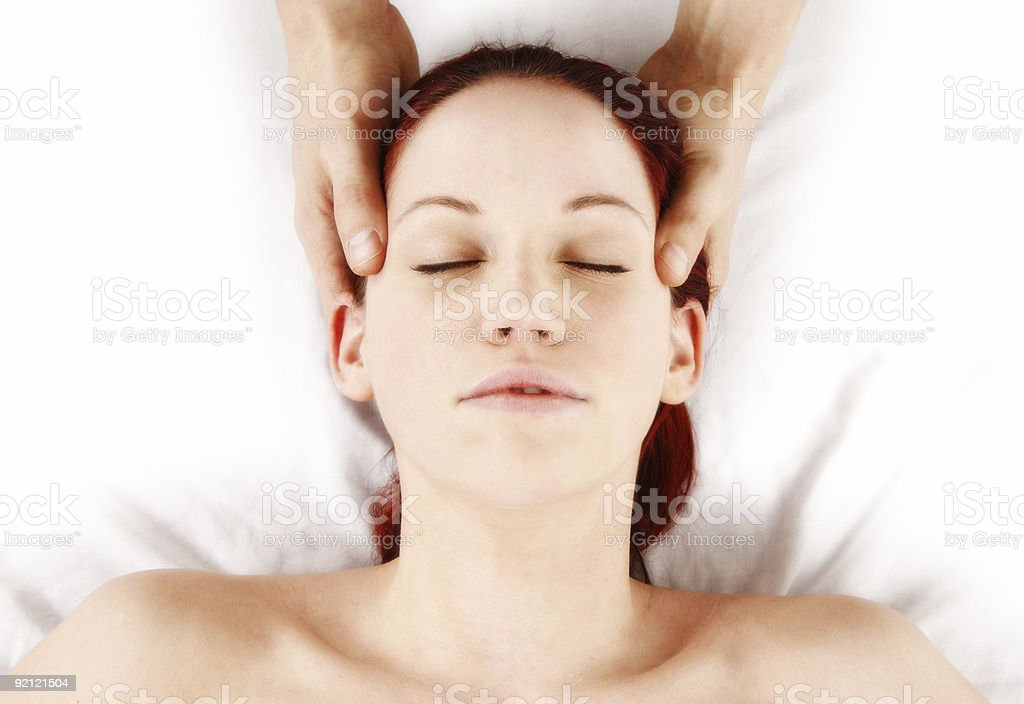 Woman receiving a massage with gentle hands on head royalty-free stock photo