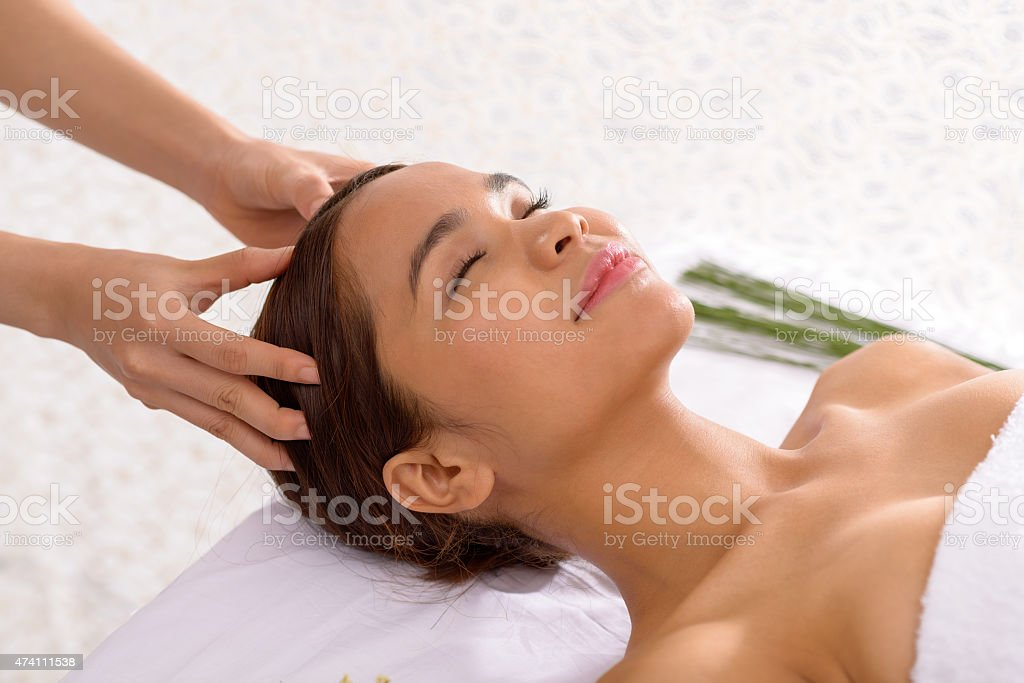 A woman receiving a scalp massage stock photo