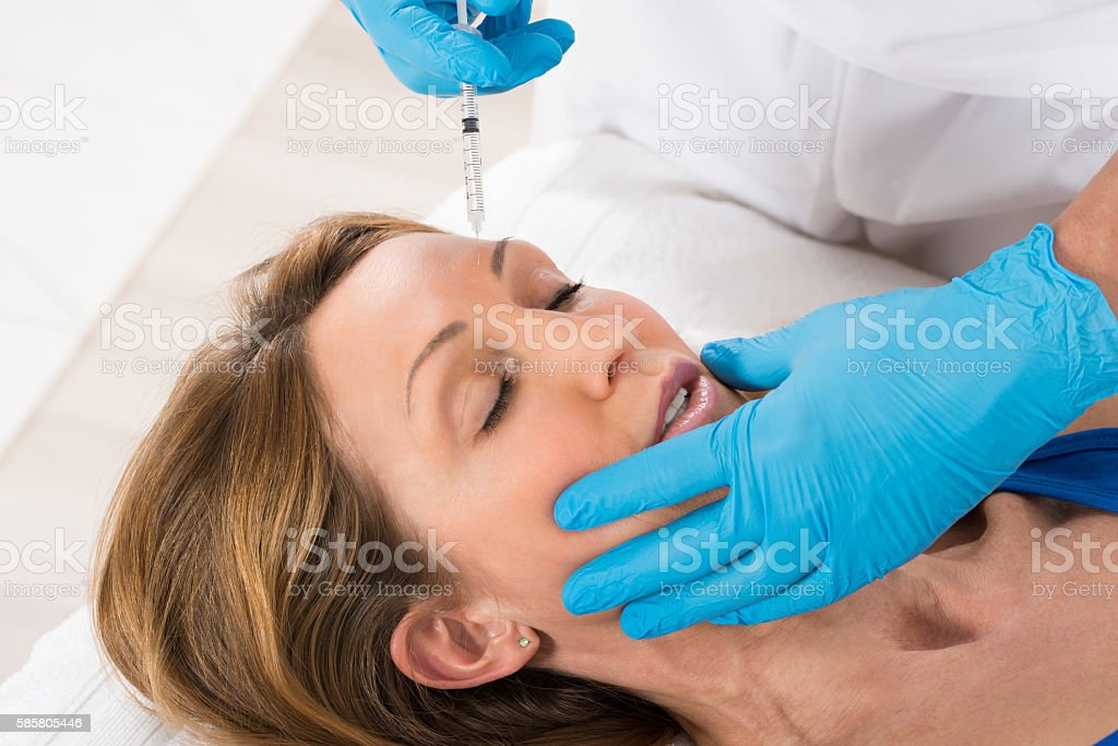 Woman Receiving Cosmetic Injection With Syringe stock photo