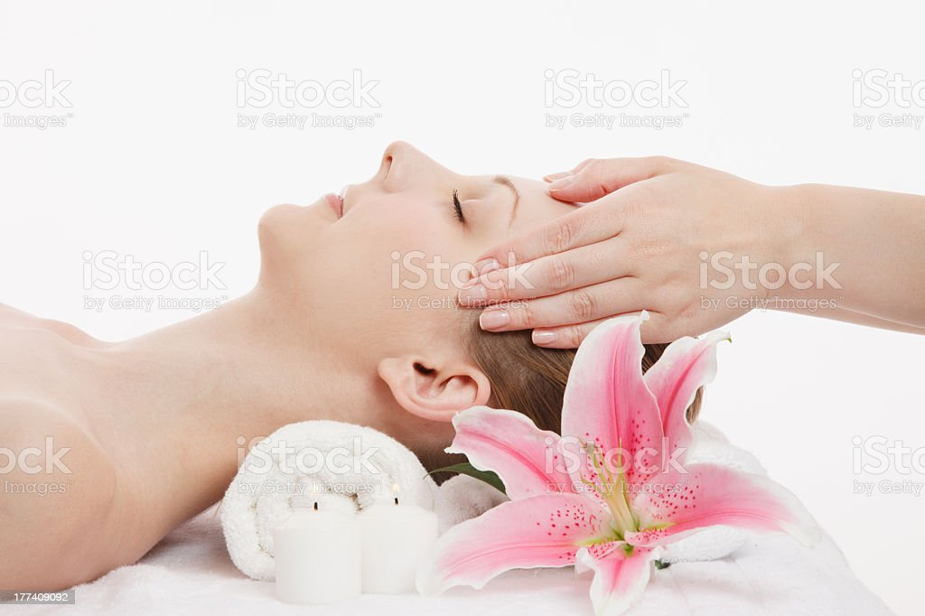 Woman receiving facial massage on white cot stock photo
