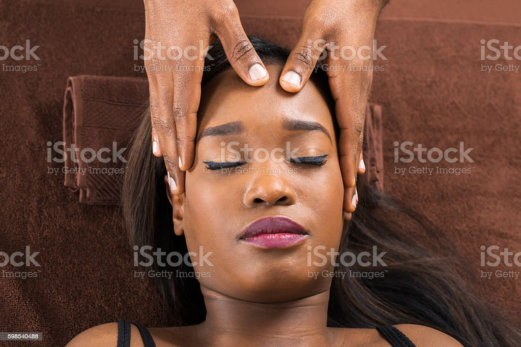 Woman Receiving Forehead Massage In Spa stock photo