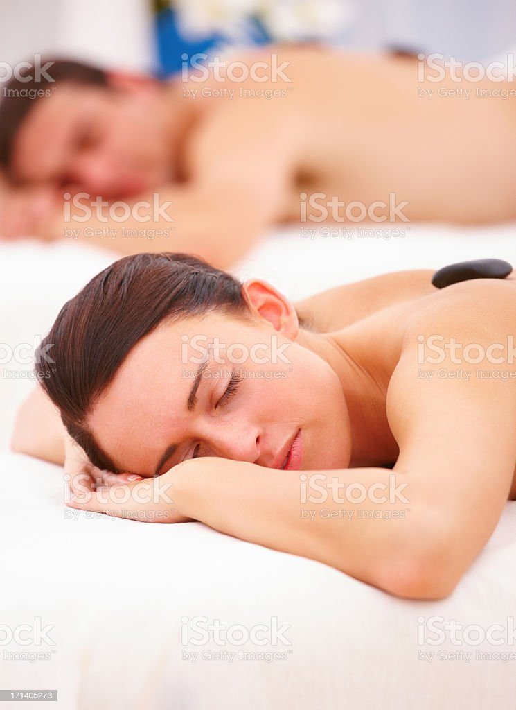 Woman receiving hotstone massage at spa stock photo