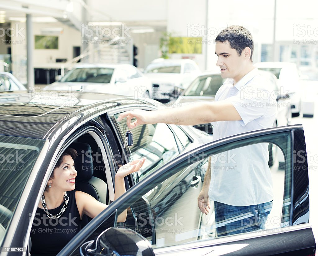 Woman receiving keys of her new car royalty-free stock photo