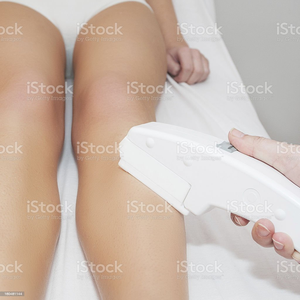 Woman receiving laser epilation treatment on her legs stock photo