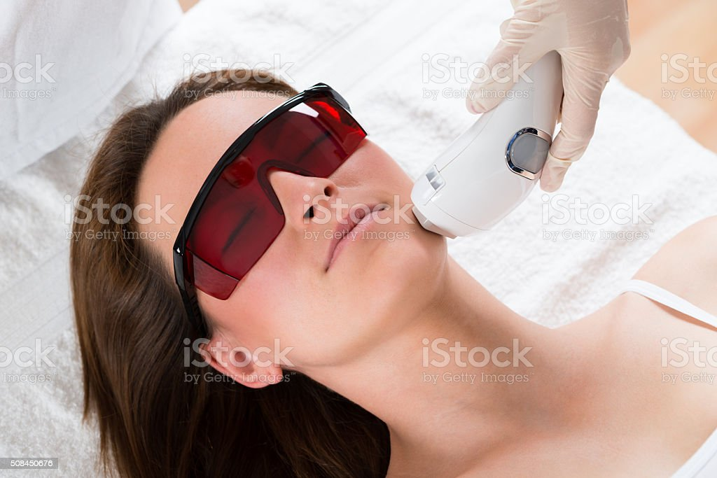 Woman Receiving Laser Epilation Treatment stock photo