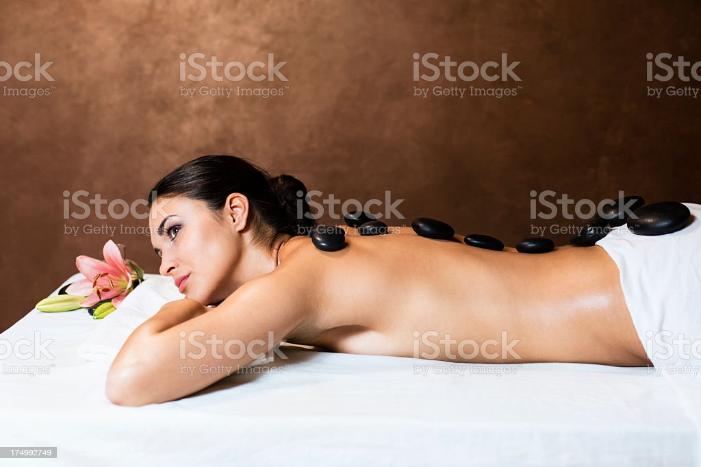 Woman receiving lastone therapy with warm stones royalty-free stock photo