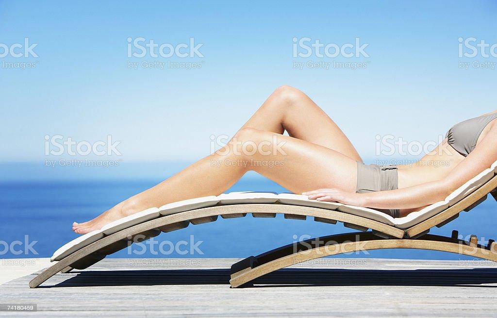 Woman reclining on folding chair in bikini outdoors royalty-free stock photo