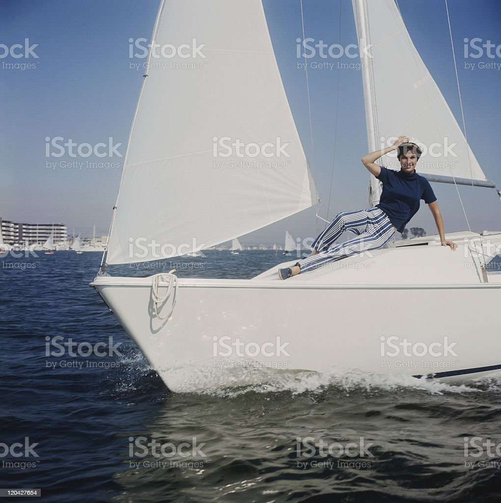 Woman reclining on sailing boat, portrait stock photo
