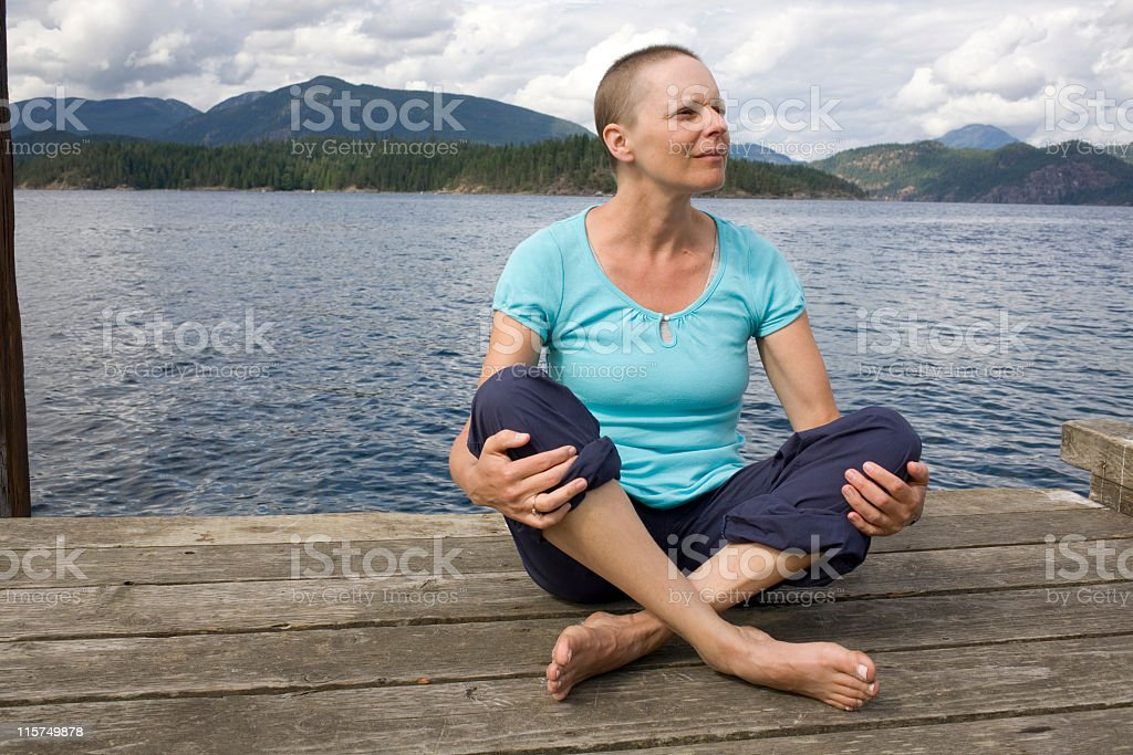 Woman recovering from breast cancer sitting on a dock. royalty-free stock photo