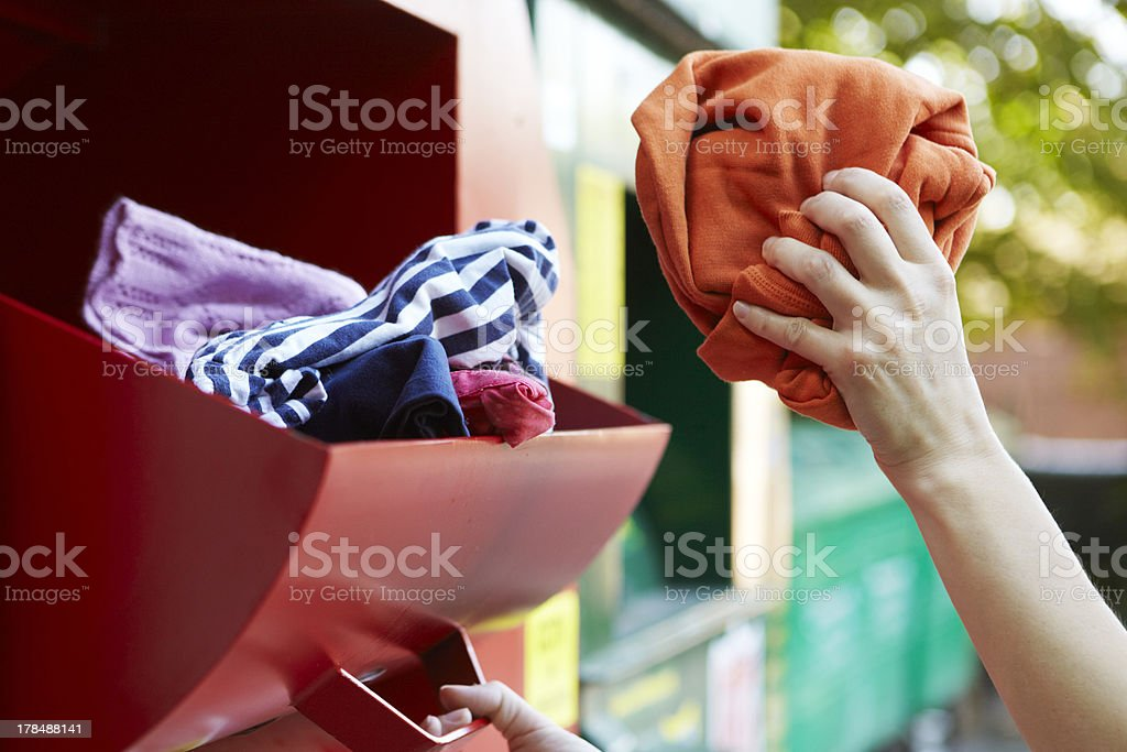 Woman Recycling Clothes At Clothing Bank stock photo