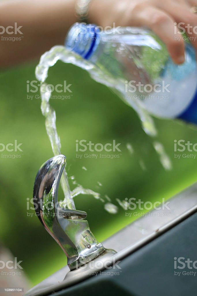 Woman Refilling a Plastic Water Bottle - Outdoors stock photo