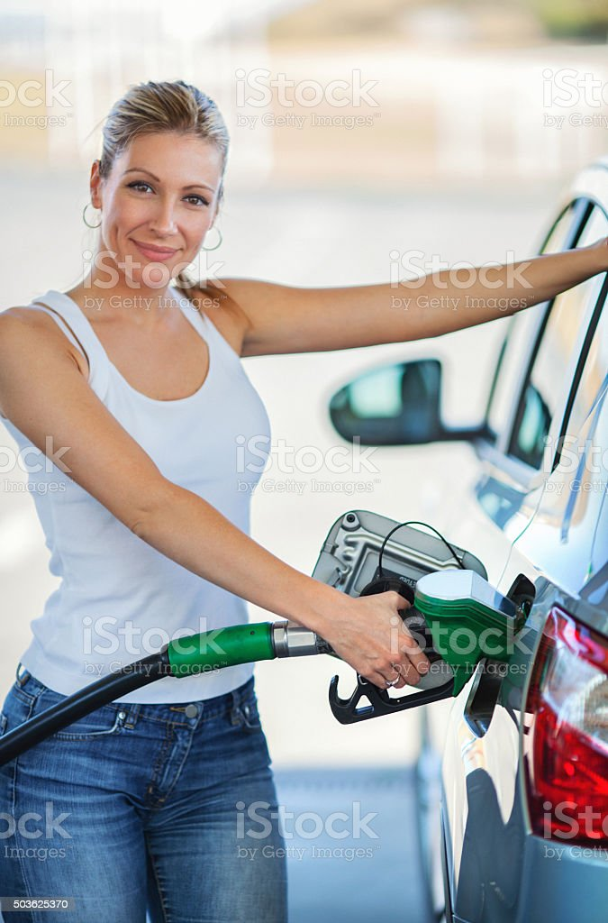 Woman refueling her car at gas station. stock photo