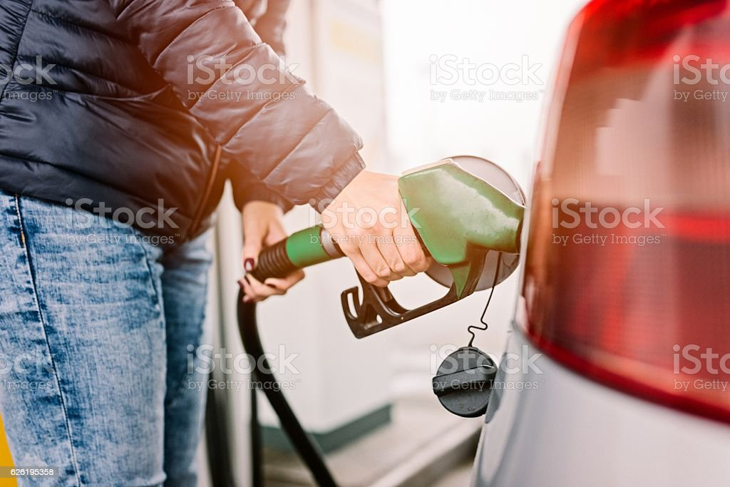 Woman refueling her small silver car stock photo