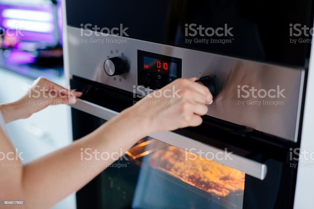 Woman regulates the time of the baking stock photo