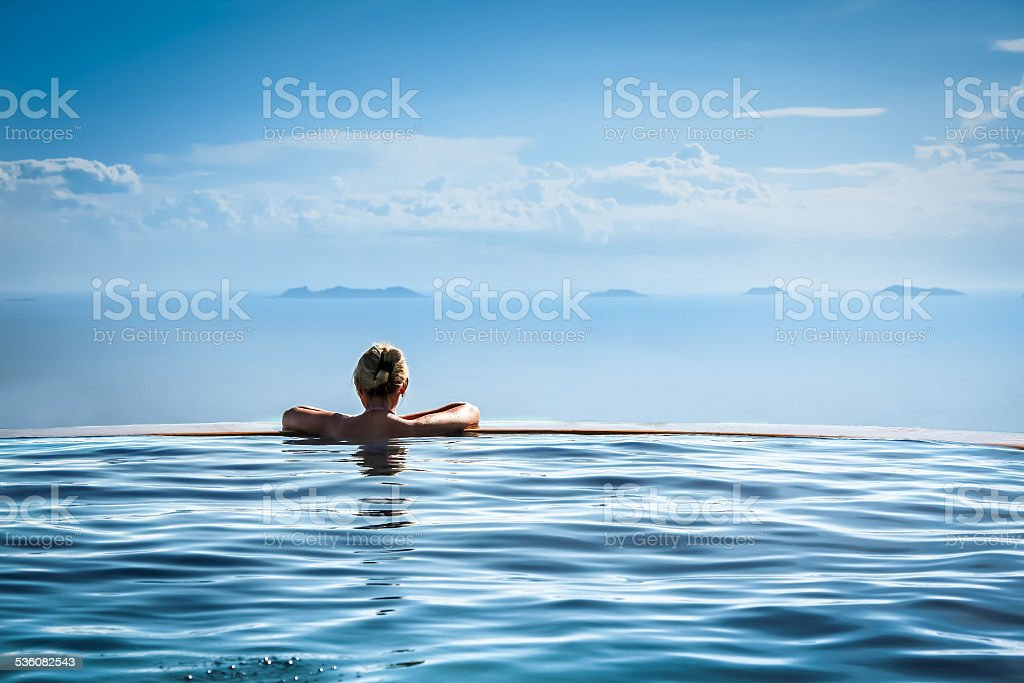 Woman relax in infinity swimming pool on vacation stock photo
