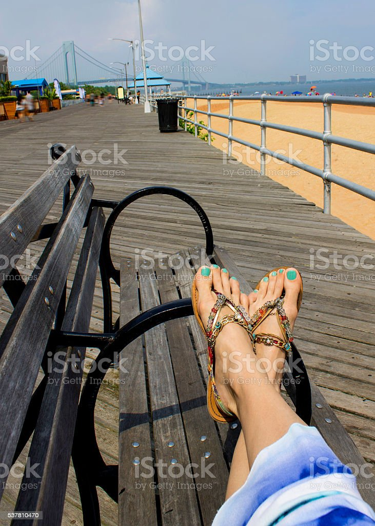 Woman relaxation on bench on boardwalk. stock photo