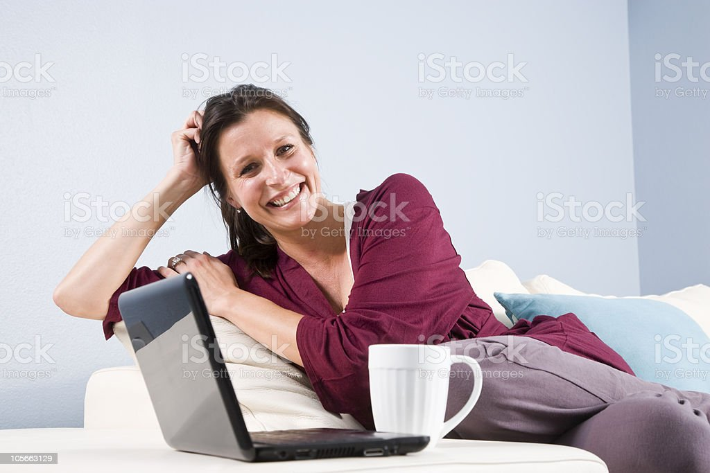 Woman relaxed on couch with laptop and coffee cup royalty-free stock photo
