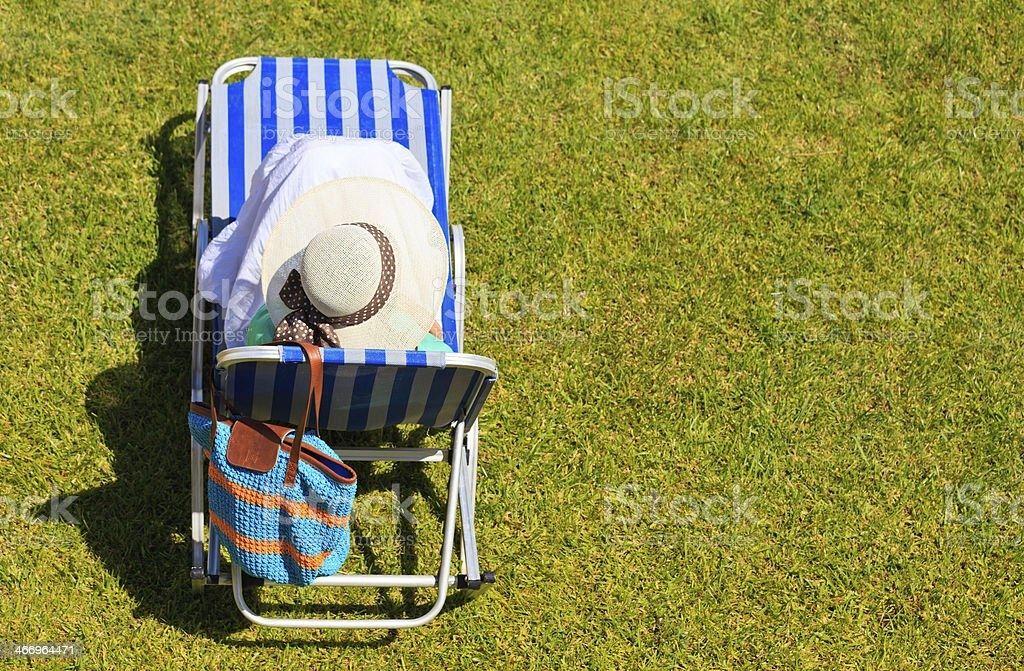 woman relaxed on lawn chair in the park royalty-free stock photo
