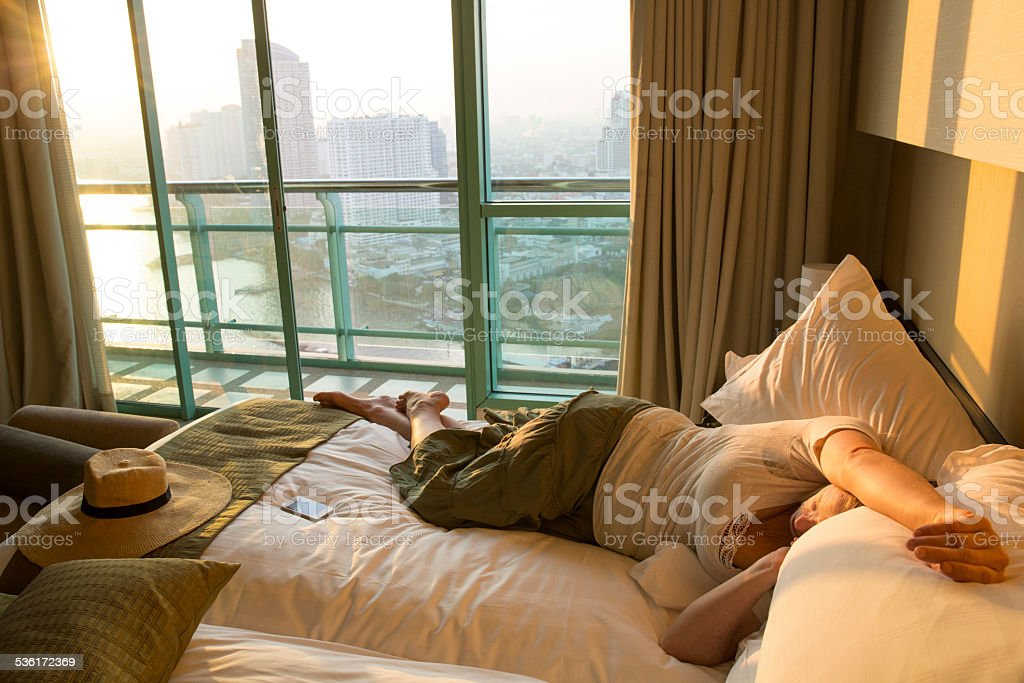 Woman relaxes in hotel room, asleep on bed stock photo