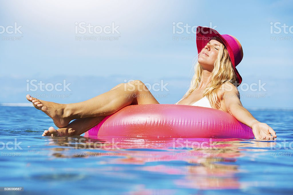 Woman relaxing and floating in the ocean stock photo