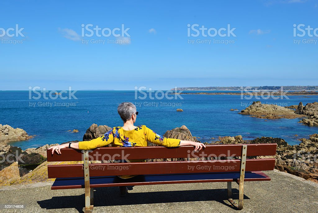 Woman Relaxing and Looking at Beach View stock photo