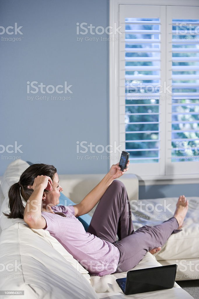 Woman relaxing and looking at text messages royalty-free stock photo