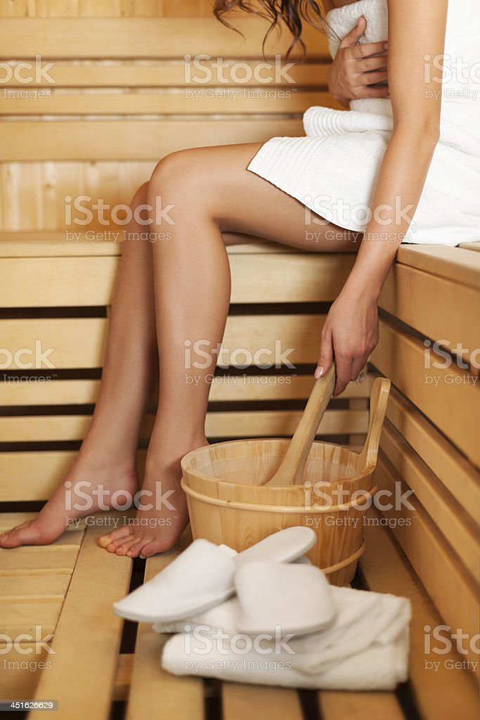 Woman relaxing and using sauna accessories stock photo