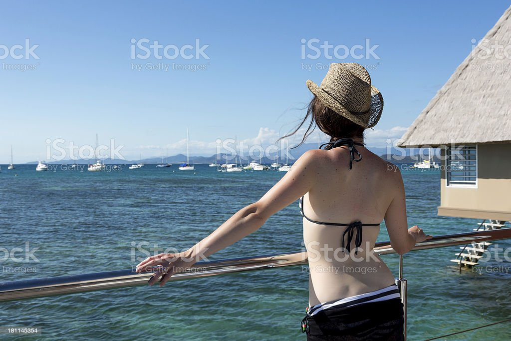 Woman Relaxing and Wearing a Hat at Tropical Resort royalty-free stock photo
