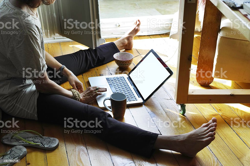Woman Relaxing and Working On The Floor With Laptop Coffee stock photo
