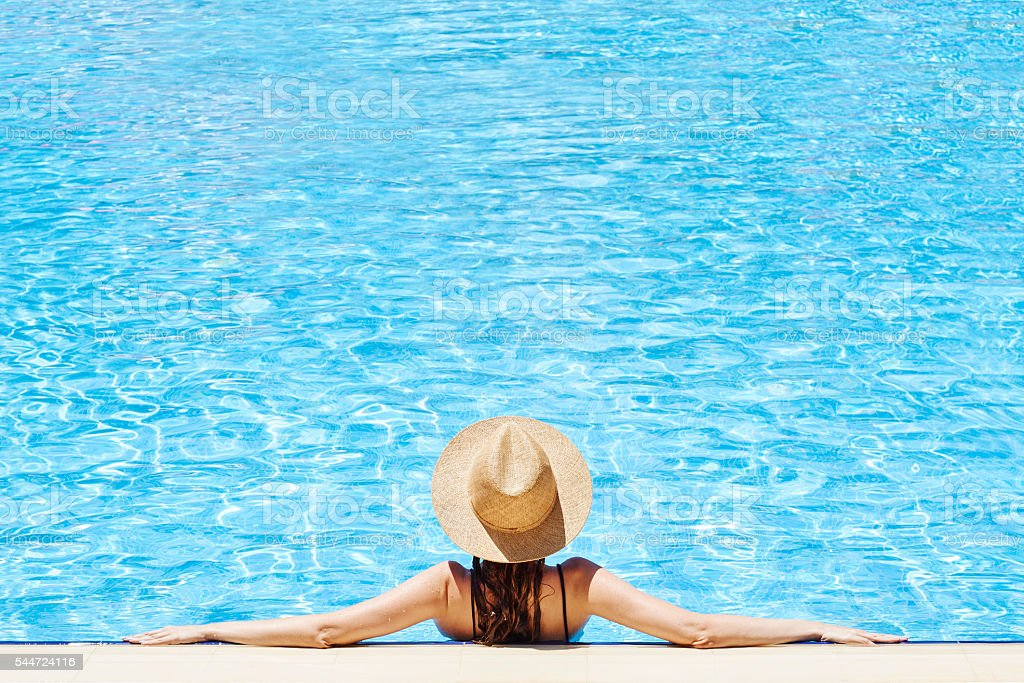 Woman Relaxing at a Resort Swimming Pool stock photo