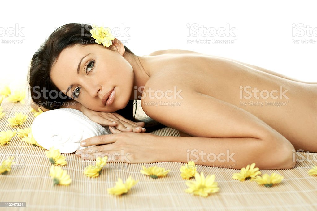 A woman relaxing at a spa with yellow flowers royalty-free stock photo