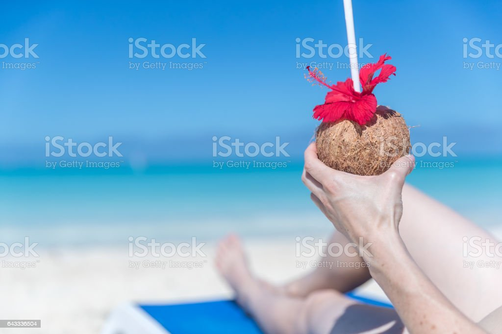 Woman Relaxing at Beach with Tropical Drink, Cuba stock photo