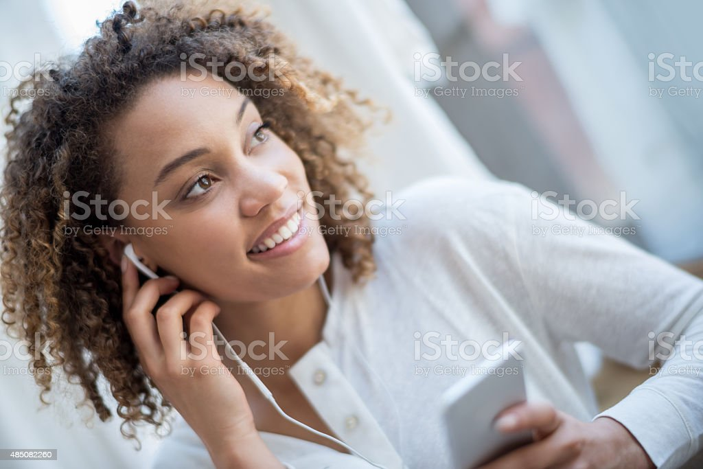 Woman relaxing at home listening to music stock photo