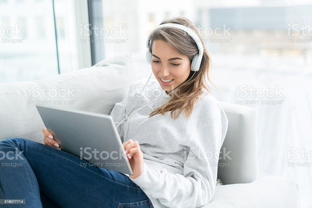 Woman relaxing at home using a digital tablet stock photo