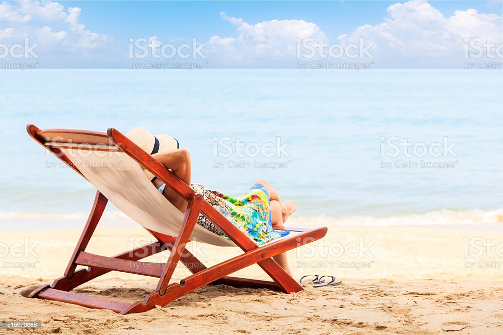Woman relaxing at the beach stock photo